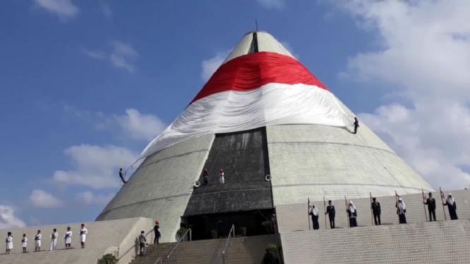 Pengibaran bendera raksasa saat upacara Hari Pahlawan di Monumen Jogja Kembali