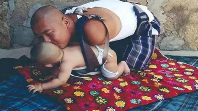 Kisah Seorang Ayah Tanpa Lengan Menggendong Anaknya