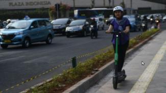 Ilustrasi pengguna skuter listrik di jalanan Jakarta