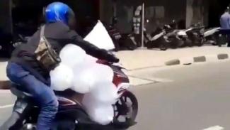 Pengendara motor bawa banyak plastik berisi es