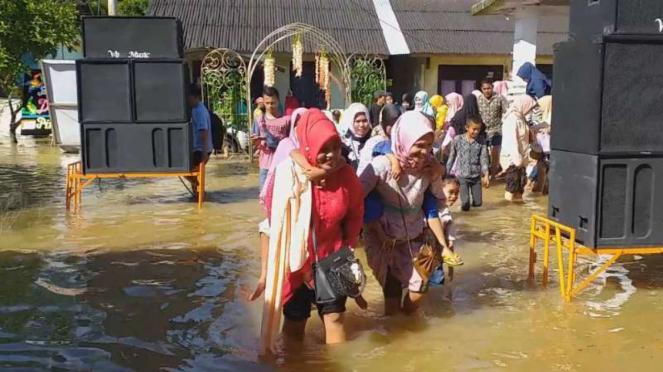 Sebuah resepsi pernikahan warga Aceh Barat, Aceh, digelar di tengah banjir yang