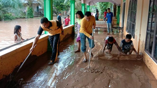 Warga Riau bersihkan area rumah dari lumpur tanah akibat terjangan banjir.