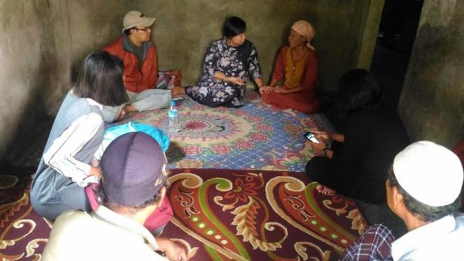 Aktivis Migrant Care Anis Hidayah, batik tengah, dengan keluarga EH di Tangerang