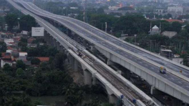 Kendaraan petugas melintas di area pengerjaan sisi sambung tol Jakarta-Cikampek.