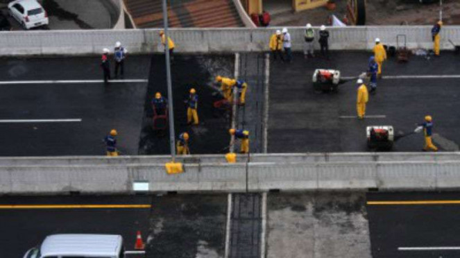 Pekerja memperbaiki sisi sambung jalan Tol layang Jakarta-Cikampek.