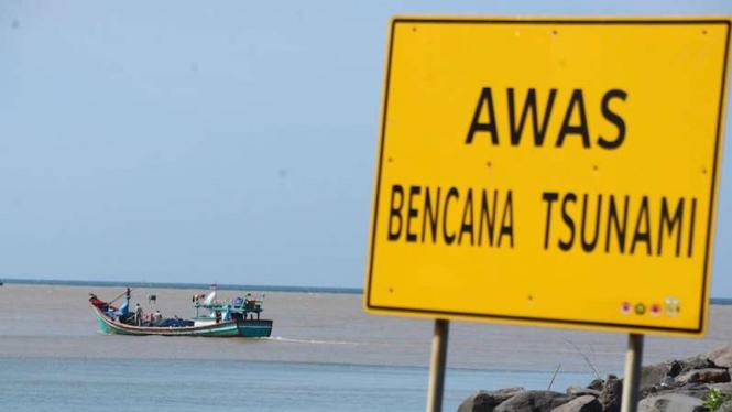 Kapal nelayan melintas di perairan pantai dipasangi rambu peringatan tsunami, Desa Kampung Jawa, Banda Aceh, Aceh, Minggu (22/12/2019). Pemasangan rambu kawasan bencana tsunami di sejumlah lokasi pantai daerah itu merupakan peringatan bagi warga pesisir.