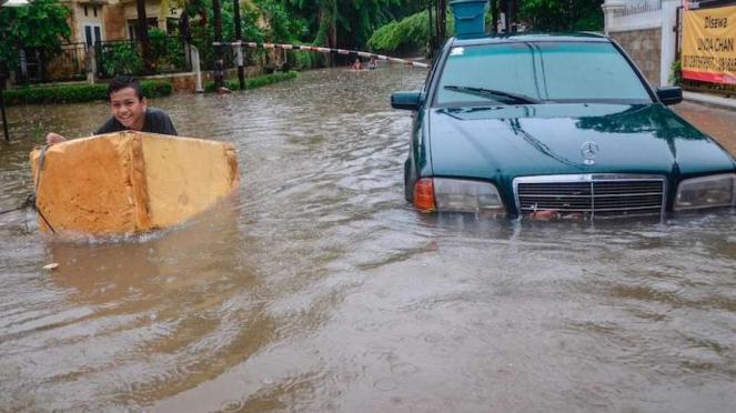 Sejumlah anak bermain saat banjir di Duren Sawit, Jakarta Timur, Rabu (1/1/2020). Menurut warga banjir mulai merendam areal sekitar perumahan pada pukul 04.00 WIB.