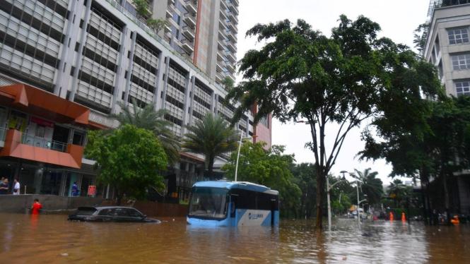 Mobil dan bus Transjakarta terendam banji.