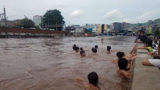 Aksi 'Bocah' Kampung Pulo, Jakarta Timur berenang di arus banjir