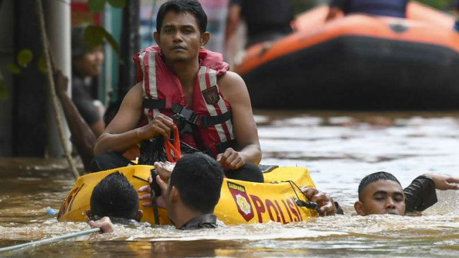 Polisi evakuasi warga yang terkena banjir di Kampung Melayu, Jakarta  Timur
