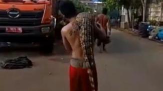 Pemuda menggendong buaya yang ditemukan di sungai Pesanggrahan