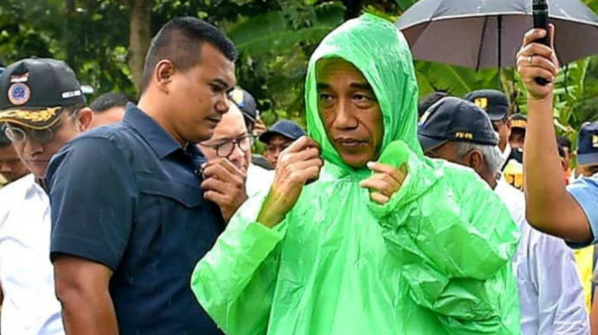 Presiden Joko Widodo meninjau longsor di Sukajaya sambil kehujanan.