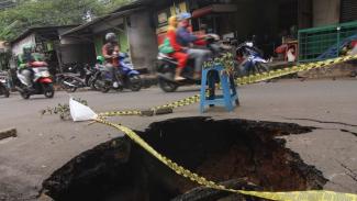 Sejumlah pengendara melintas di jalan yang amblas di kawasan Cibubur, Jakarta Timur, Kamis (2/1/2020). Kondisi jalan tersebut mengalami kerusakan di satu sisi jalan yang dapat membahayakan pengendara yang melintas terutama pada malam hari.