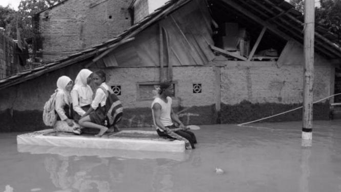 Menerjang banjir ke sekolah (Gambar: Merdeka.com)