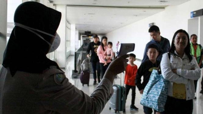 Petugas melakukan pendeteksi suhu tubuh di Bandara Juanda, Surabaya.
