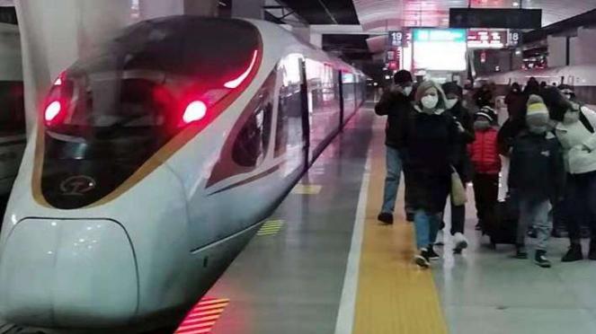 Para penumpang kereta cepat baru tiba di Stasiun Tianjin, Kamis (22/1) malam, dengan mengenakan masker untuk menghindari wabah virus corona jenis baru di Wuhan, China.