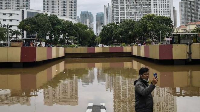 Warga berswafoto saat banjir menutup underpass di jalan Kota Baru Bandar Kemayoran Jakarta, Jumat (24/1/2020). Banjir dikawasan tersebut diakibatkan intensitas hujan yang tinggi dan drainase yang buruk.