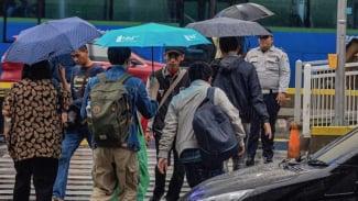 Warga berjalan menggunakan payung saat turun hujan di Jakarta.