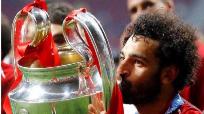 Winger Liverpool, Mohamed Salah, mencium trofi Liga Champions.