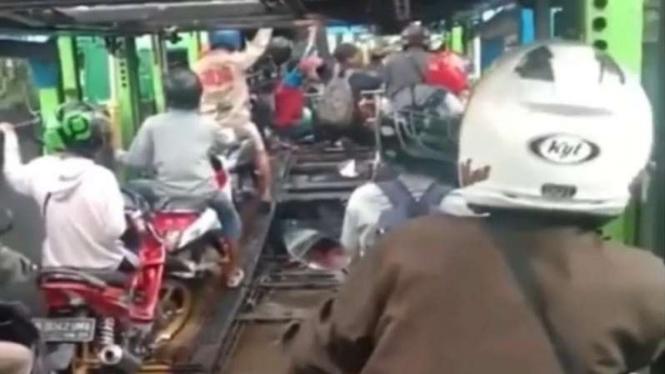 Pengendara sepeda motor menumpang truk untuk melintasi jalanan banjir