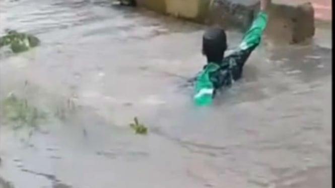 Supir ojek online yang tercebur di lobang tertutup air saat banjir