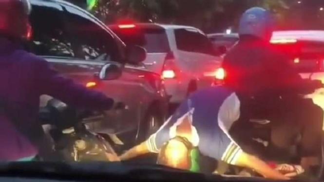 Pembonceng menunjukkan aksi tak biasa di atas sepeda motor.
