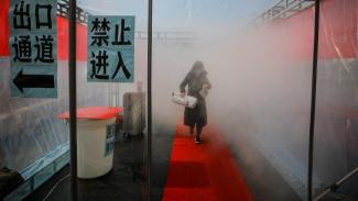 eorang wanita tengah di semprot desinfekta dipintu masuk komplek Perumahan di Tianjin (Image Credit: China News Service)