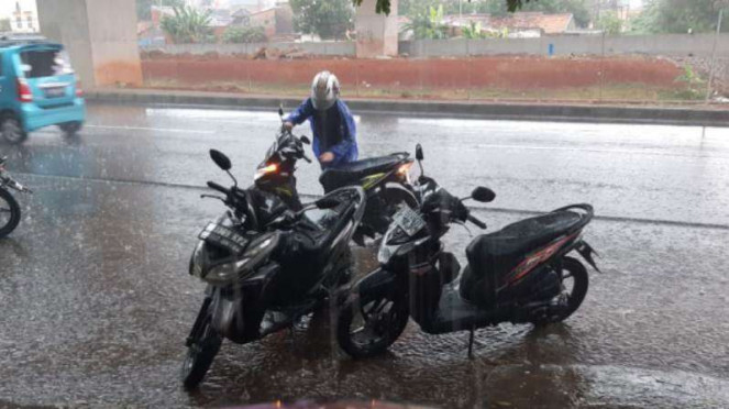 Pengendara motor tampak menepi akibat hujan deras di Kalimalang, Jakarta.