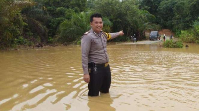 Seorang petugas polisi menunjukkan banjir di Penajam Paser Utara.