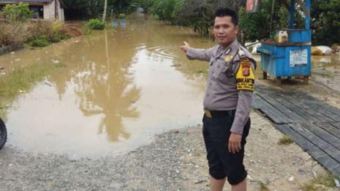 Seorang petugas polisi menunjukkan banjir yang merendam Penajam Paser Utara.