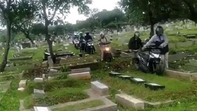 Aksi pemotor melewati area pemakaman untuk potong jalan.