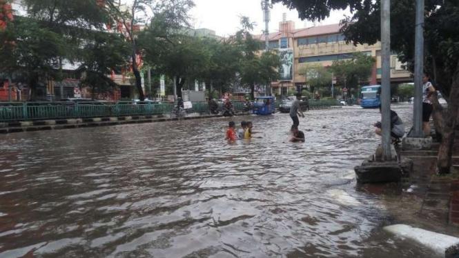 Anak-anak di Mangga Dua, Jakarta Barat, asyik berenang di genangan banjir.