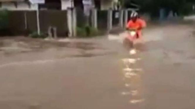 Pengendara motor trail Honda CRF mencoba melibas genangan banjir