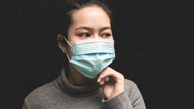 Wanita pakai masker.