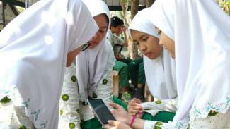 Siswa di SMA Khadijah Surabaya mempraktikkan cara kerja aplikasi Care With Straat Kinderen.