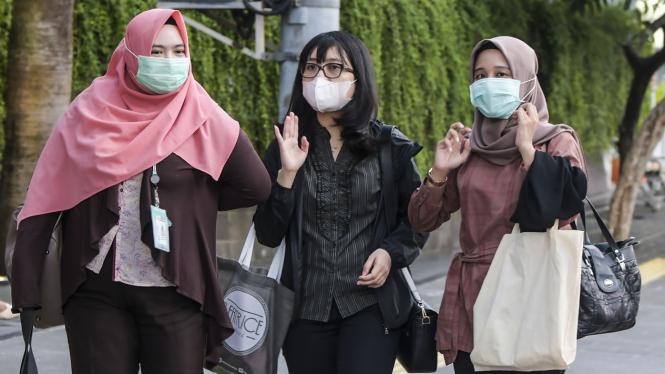 Warga memakai masker sebagai cara mengantisipasi penyebaran virus corona.