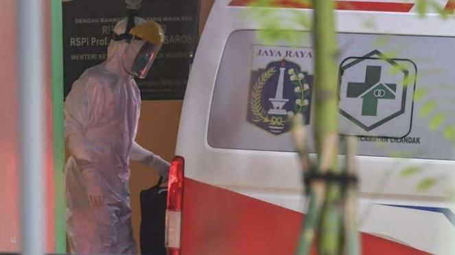 Petugas membawa barang milik pasien ke ruang isolasi di RSPI Sulianti Saroso