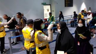Petugas bandara Soekarno Hatta memeriksa suhu tubuh penumpang