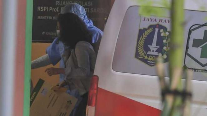 Petugas membawa seorang wanita yang diduga terinfeksi virus COVID-19