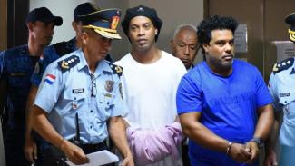 Ronaldinho dengan tangan diborgol sehabis jalani sidang di pengadilan Paraguay.