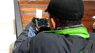 Pengendara ojol bermain ponsel.