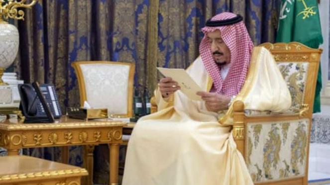 Raja Salman membaca dokumen ketika ia menerima dua duta besar Saudi yang baru diangkat di istananya.