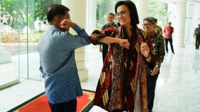Mantan Wapres Jusuf Kalla dan Menkeu Sri Mulyani melakukan salam corona.