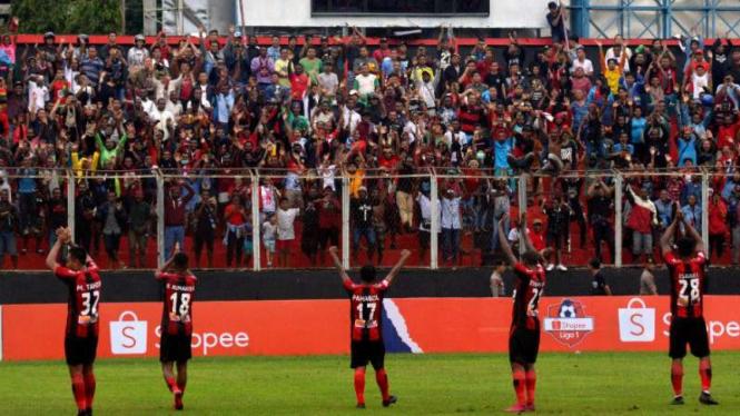 Pemain Persipura Jayapura merayakan kemenangan di hadapan suporter.