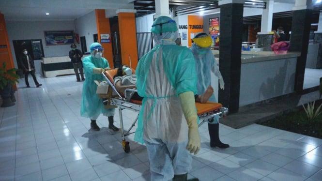 Perawat bawa pasien dalam pengawasan virus corona COVID-19.