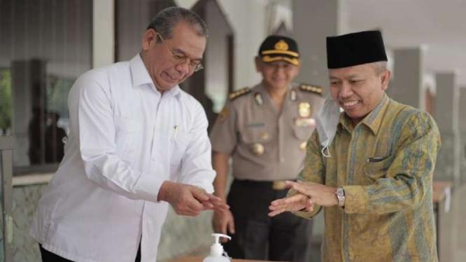 Direktur Bina Haji Khoiri dan Direktur Jenderal Penyelenggaraan Haji dan Umrah Nizar mencuci tangan sebelum memasuki ruang tes calon petugas haji di Asrama Haji, Pondok gede, Jakarta, Rabu, 18 Maret 2020.