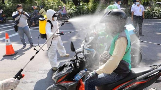 Petugas BPBD Jatim melakukan penyemprotan disinfektan kepada pengojek online
