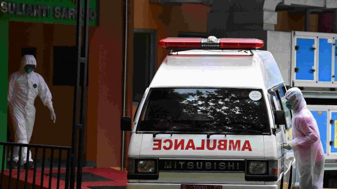 Petugas penanganan Covid-19 berjalan ke mobil ambulans.
