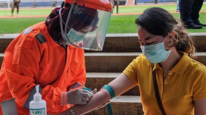 Petugas medis mengecek kesehatannya dengan mengambil sampel darah dengan metode rapid test (pemeriksaan cepat) di Stadion Patriot Candrabhaga, Bekasi, Jawa Barat, Rabu (25/3/2020).