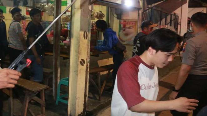 Aparat kepolisian membubarkan pengunjung di warung kopi di Surabaya